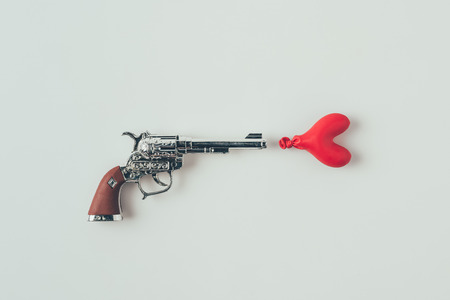 top view of gun aiming at heart shaped balloon isolated on white Stock Photo