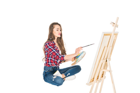 beautiful young woman painting picture isolated on white