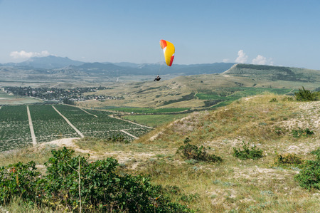 Parachute in the sky over field in hillside area of Crimea, Ukraine, May 2013 Stock Photo