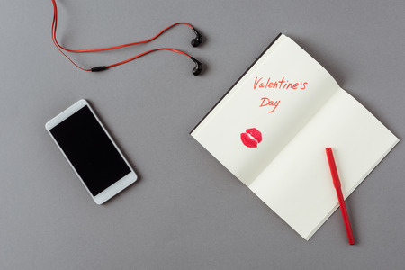 top view of smartphone and notebook with lips print on gray surface Stok Fotoğraf - 111951774