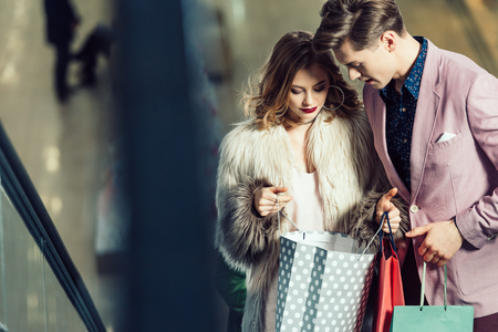 young stylish couple looking into shopping bags at mall Фото со стока