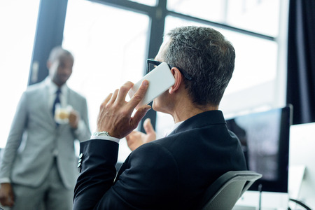 selective focus of businessman talking on smartphone in office