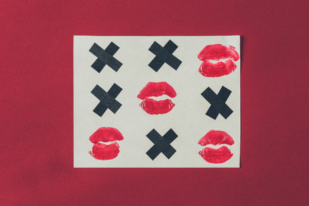 top view of tic-tac-toe with black crosses and lips prints isolated on red Banco de Imagens