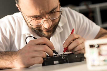 man using multimeter while testing hard disk drive Standard-Bild - 111952184