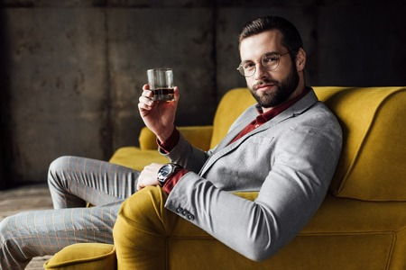 stylish handsome man holding glass of whiskey and looking at camera