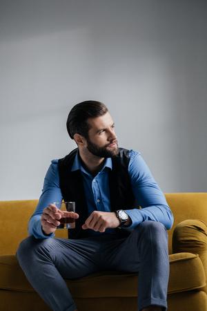stylish man holding alcohol drink and sitting on yellow sofa Фото со стока