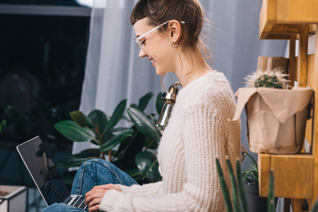 side view of smiling girl sitting with laptop on table in office