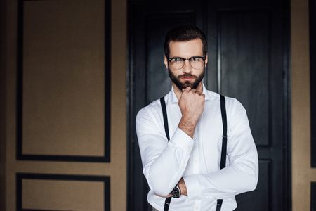 thoughtful elegant man posing in white shirt and suspenders