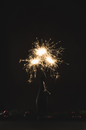 close up view of burning sparklers in bottle and christmas balls isolated on black Stock Photo