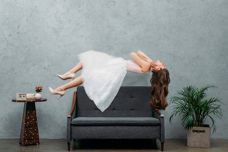 beautiful barefoot girl hovering above couch