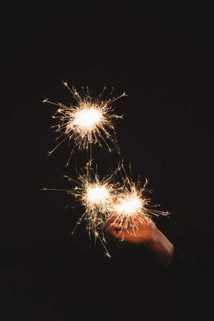 partial view of woman holding burning sparklers  in hand isolated on black