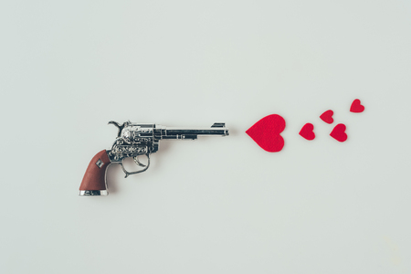 top view of gun aiming at paper hearts isolated on white