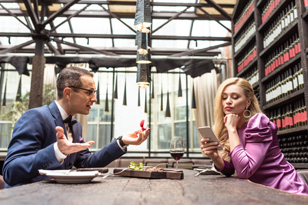 man proposing his girlfriend while she using smartphone with bored expression at restaurant Stock Photo
