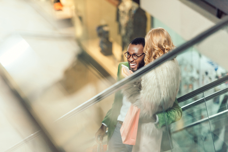 stylish young couple riding escalator and embracing at shopping mall Standard-Bild