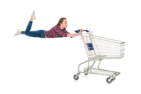 happy young woman levitating with empty shopping trolley isolated on white Stock fotó