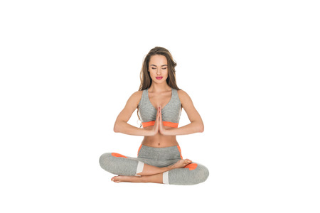 young woman with closed eyes sitting in lotus position isolated on white