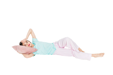 girl in pajamas lying on pillow with closed eyes isolated on white