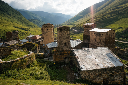 view of grassy field with old weathered rural buildings and hills on background, Ushguli, svaneti, georgia