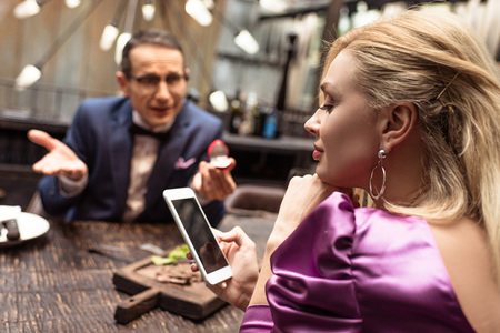 man proposing his girlfriend while she using smartphone at restaurant