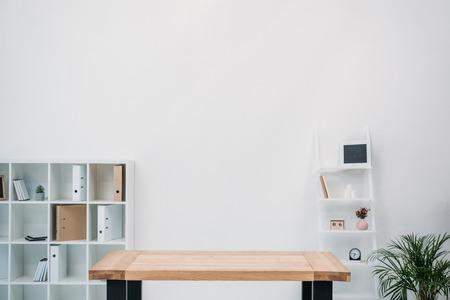 intérieur de bureau moderne avec table en bois vide et dossiers sur étagères