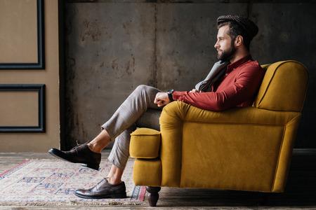 modischer bärtiger Mann, der auf gelbem Sofa sitzt Standard-Bild