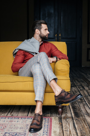 fashionable man in suit and brogue shoes sitting on yellow sofa in loft interior