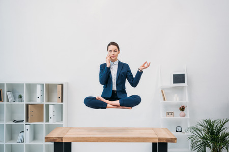 businesswoman talking by smartphone while levitating in office