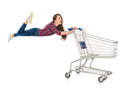 young woman levitating with empty shopping trolley isolated on white