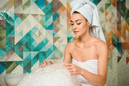 Jeune femme regardant la mousse dans le bain turc Banque d'images
