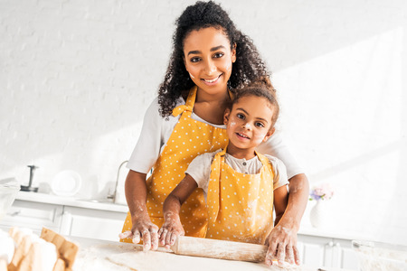 cheerful african american mother helping daughter rolling dough with rolling pin in kitchen, looking at camera Stock Photo