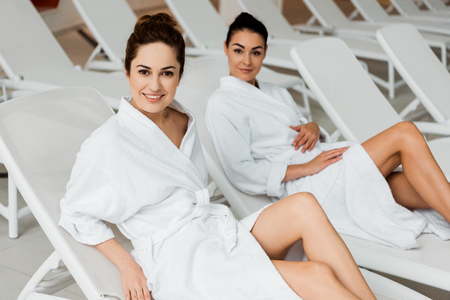 attractive young women in bathrobes resting on sunbeds and smiling at camera in spa Stock Photo