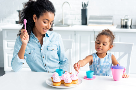 african american mother and daughter eating homemade cupcakes in kitchen Stok Fotoğraf