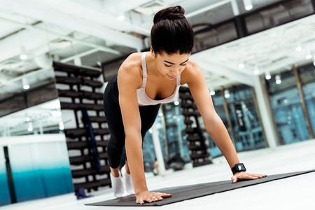 Attractive strong girl doing plank on mat in sports gym Imagens