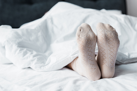 cropped view of girl in socks lying under white blanket in bed