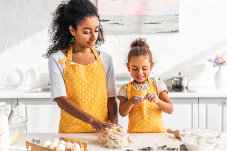african american mother and daughter preparing dessert and kneading dough in kitchen