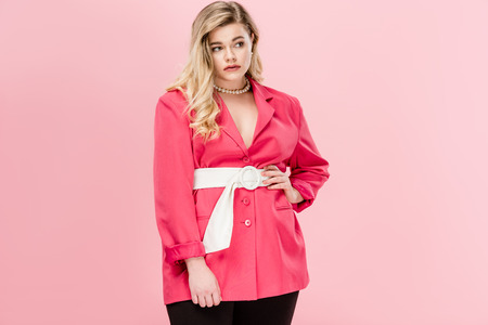 beautiful fashionable young oversize woman looking away isolated on pink