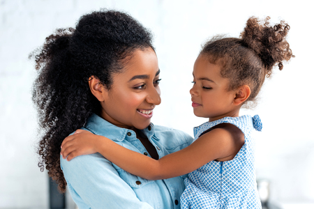 smiling african american mother and daughter hugging in kitchen and looking at each other