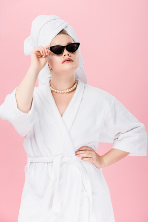young oversize woman in bathrobe, sunglasses and towel on head posing with hand on waist isolated on pink Stok Fotoğraf