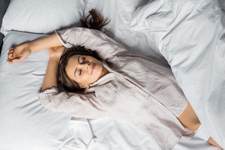 bovenaanzicht van jonge aantrekkelijke vrouw in pyjama die 's ochtends op bed slaapt Stockfoto