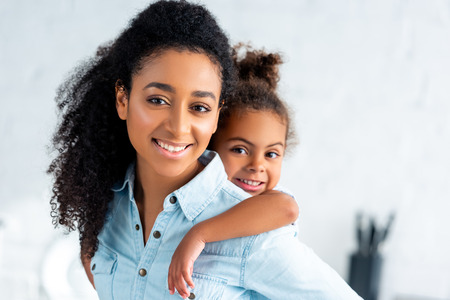 cheerful african american mother giving piggyback to adorable daughter in kitchen