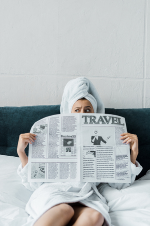 confused girl hiding behind travel newspaper while resting on bed in the morning