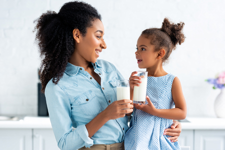 cheerful african american mother and daughter holding glasses of milk in kitchen and looking at each other