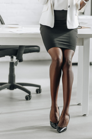 cropped view of legs of african american businesswoman in formal wear in office Stockfoto