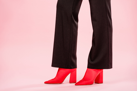 low section of young woman in stylish black pants and red shoes standing on pink Stock Photo