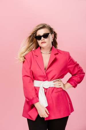 attractive oversize girl in pink trench coat and sunglasses posing with hand on waist isolated on pink Stok Fotoğraf
