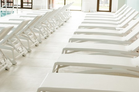 empty white sunbeds near pool in spa center Stock Photo