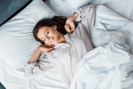 Atractiva mujer joven en pijama despertando en la cama por la mañana