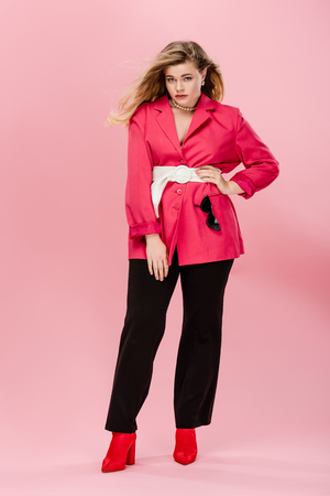 beautiful oversize woman in pink jacket standing with hand on waist and looking at camera isolated on pink Stok Fotoğraf