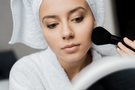 beautiful girl in bathrobe and towel applying powder with cosmetic brush Stok Fotoğraf