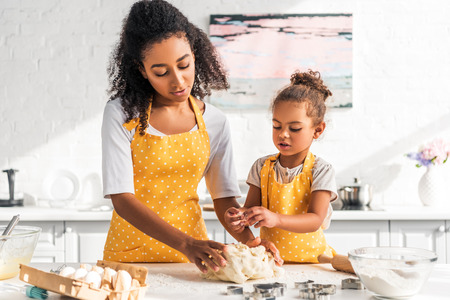 african american mother and daughter in yellow aprons kneading dough in kitchen